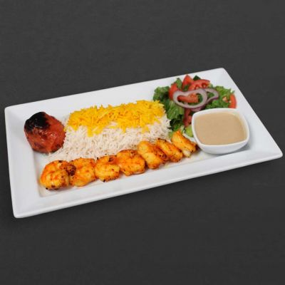 Shrimp skewer with rice, tomato, salad, and sauce.