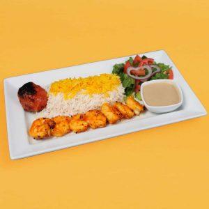 Shrimp plate with rice, tomato, salad, and tahini sauce.