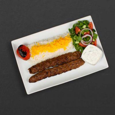 Beef koobideh plate with rice, tomato, and salad.