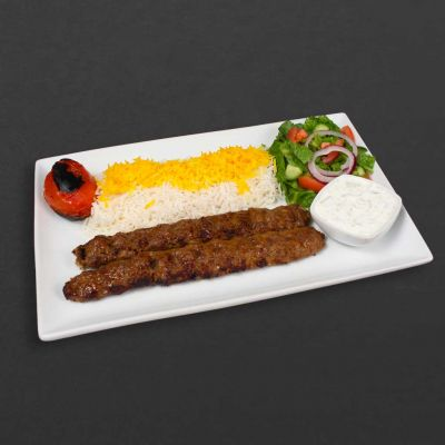 Beef koobideh plate with rice, tomato, and salad.