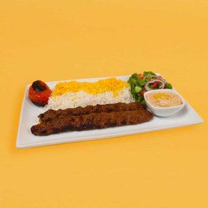 Beef koobideh plate with rice, salad. hummus, and tomato.