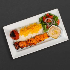 chicken kebab plate with rice, tomato, hummus, and salad.