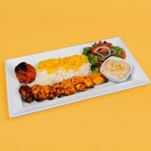 chicken kebab plate with rice, salad, tomato. and hummus.