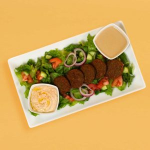 Falafel plate with salad, hummus, and tahini sauce.