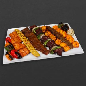 Skewer plate with salmon, chicken koobideh, barg, shish kebab, chicken kebab, beef koobideh, shrimp, and peppers.