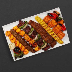Skewer plate with shrimp, beef koobideh, chicken kebab, shish kebab, barg, chicken koobideh, salmon, and peppers.