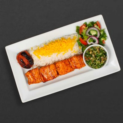 Salmon kebab plate with rice, salad, tomato, and tabouleh.
