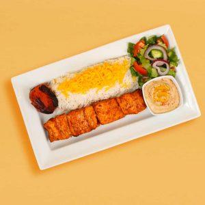 Salmon kebab plate with rice, salad, tomato, and hummus.
