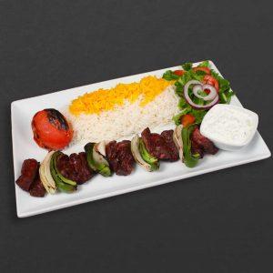 Shish kebab plate with rice, tomato, salad, and yogurt.