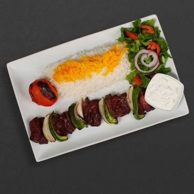 Shish kebab plate with tomato, rice, salad, and maust o khiar.